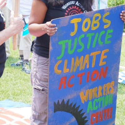Workers' Action Centre member holds placard that says, Jobs, Justice, Climate Action at rally in 2015.