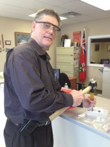 MPP Paul Miller takes a hammer and chisel to the ice.