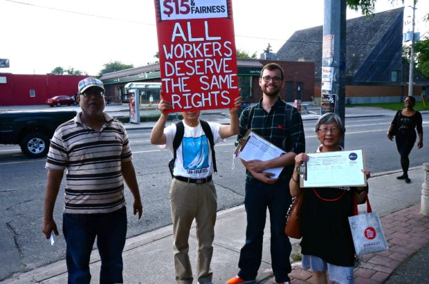 Workers' Action Centre members at 2015 Street Party holding placard that says, All workers deserve the same rights.
