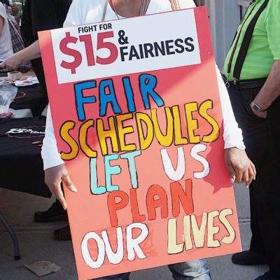 Workers' Action Centre member holds placard saying, Fair schedules let us plan our lives.