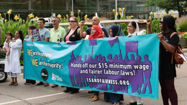 Workers and organizers with banner: Hands off our $15 minimum wage and fairer labour laws! (Labour Day 2018)